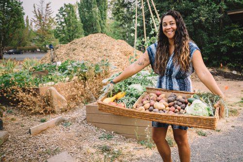 Venus Barnes holding a basket of food that she grew