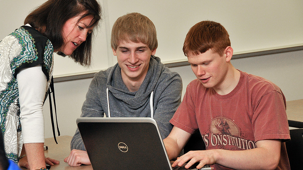Students working with an instructor at a computer