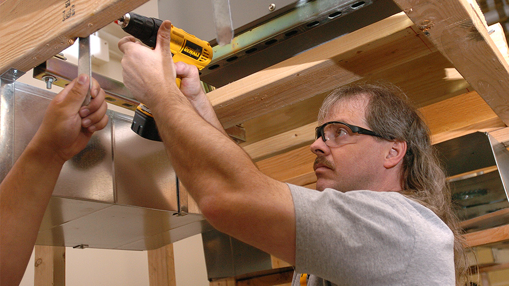 Student using a power drill on a wall frame