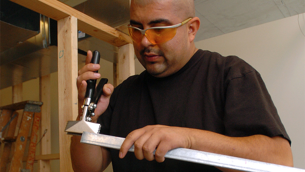 Student using a hammer with a piece of metal