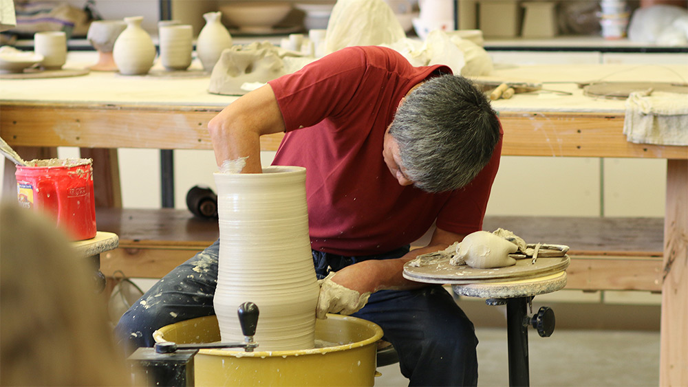 Man throwing a large pot on a pottery wheel