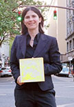 Jacqueline Ehlis holding an artwork on a street in downtown Portland