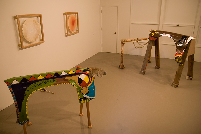 Photograph of large abstract tables that are painted brightly and resemble horses