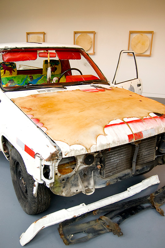 Photograph of an old white car painted over abstractly in a gallery