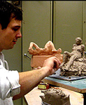 Student working on a clay sculpture of a woman