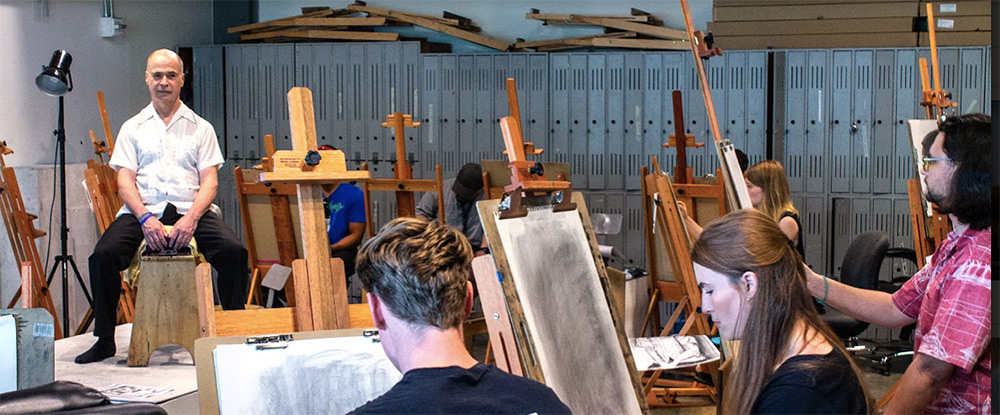 Students working with charcol to sketch a man acting as a model in the drawing studio