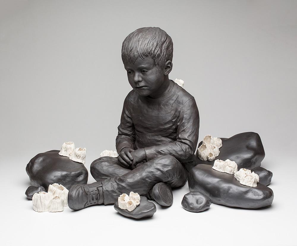 Clay sculpture of a young boy surrounded by rocks covered with barnacles