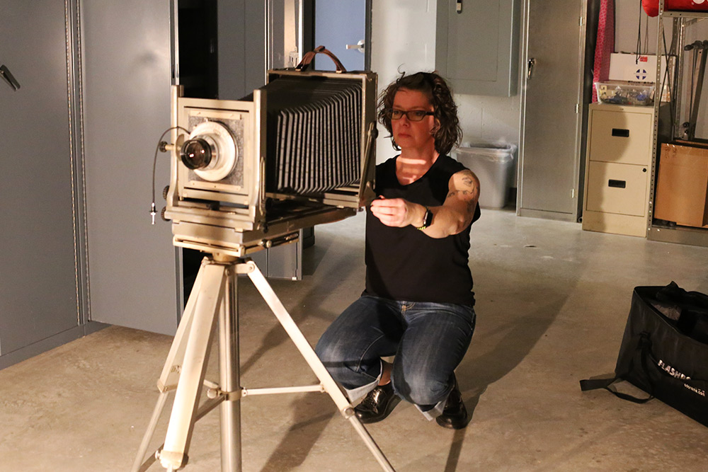 Instructor using a vintage plate camera in the studio