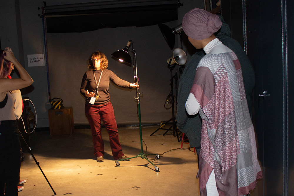 Instructor working with students in the studio on lighting