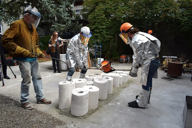 Students outside casting bronze and wearing protective gear