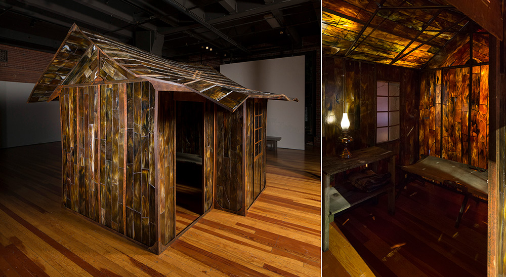 Two photographs of a small, brown, stained glass shack in an art gallery, one showing the exterior and the other the interior