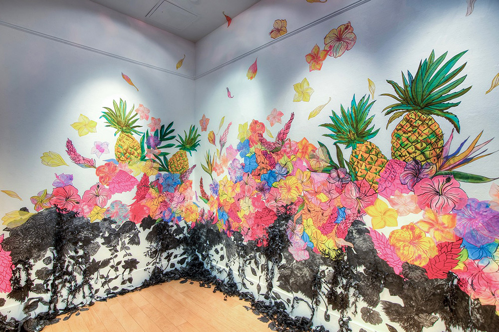 Artwork on two adjacent walls and a corner of pinapples and colorful flowers with dark, dead vines below