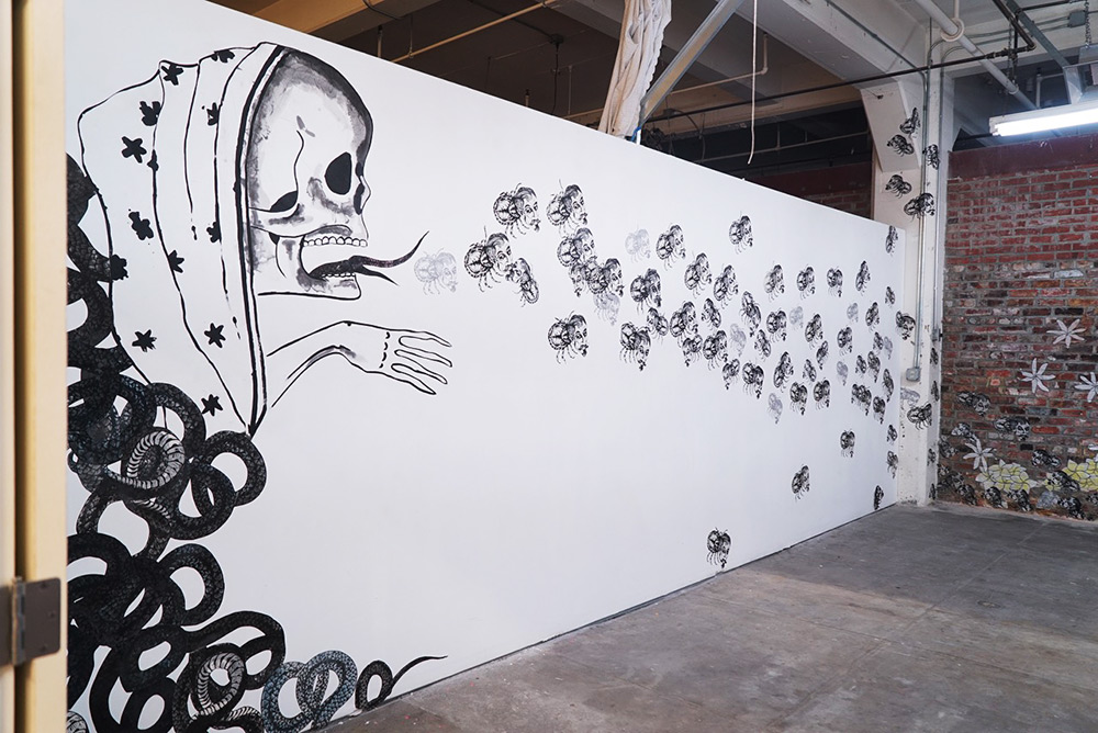 Black mural on a white wall showing a skull blowing out small skulls which are flying across the wall and up a column