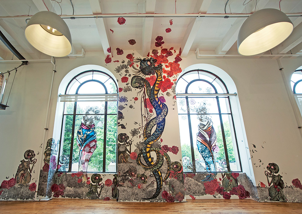 Large colorful mural up a wall between two large windows showing figures and abstract snake imagery
