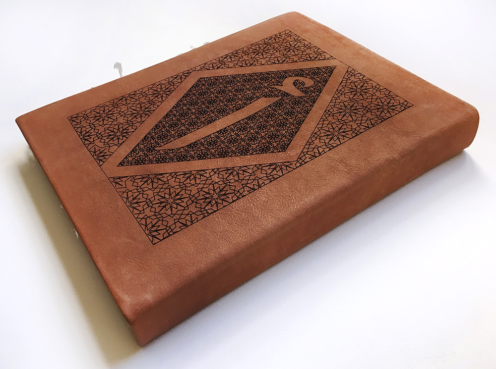 Cover of a leatherbound book embossed with calligraphy and geometric shapes
