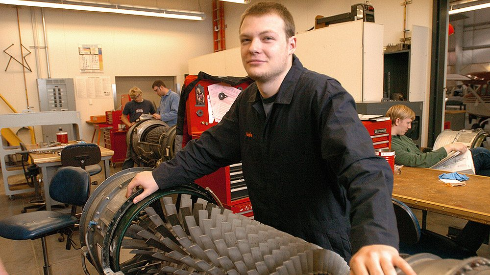 Student in the classroom with part of an engine