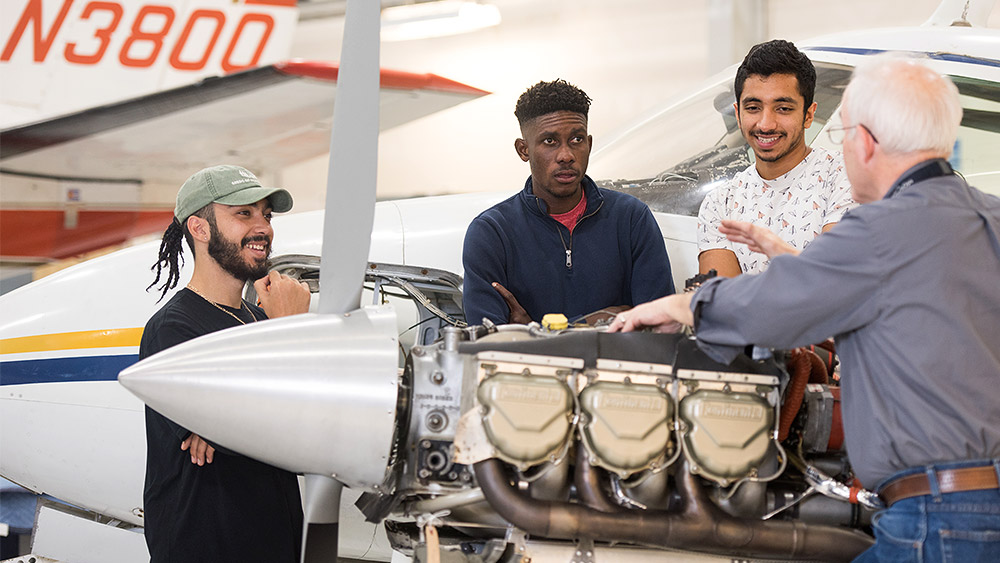 Students looking at an engine with an instructor