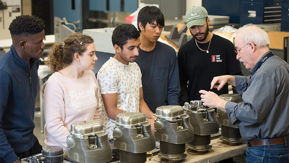 Students looking at engine parts on a table with the instructor