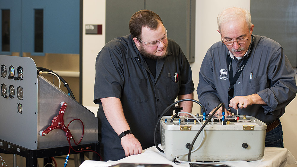 Student and instructor looking at an engine control panel electronics