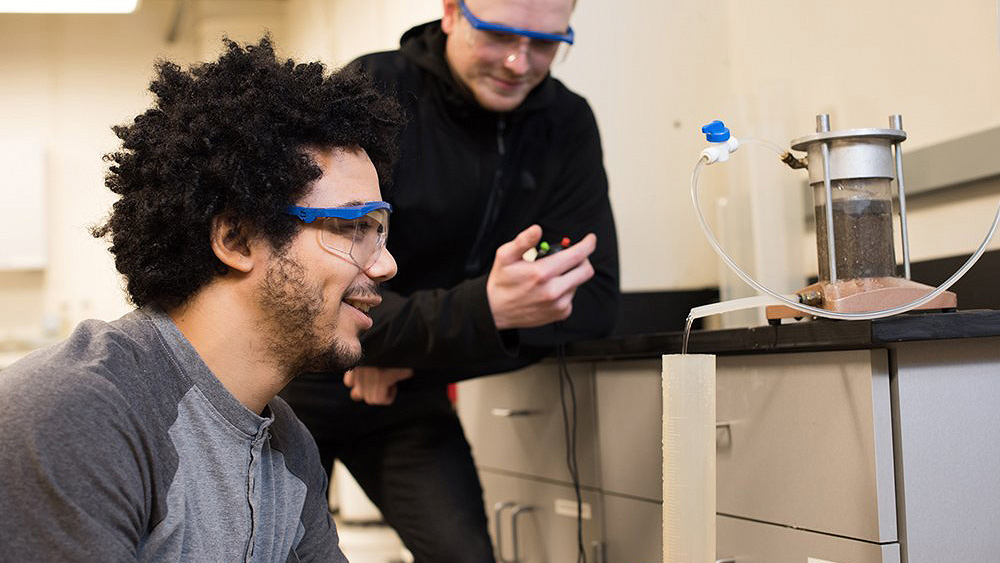 Two students performing an experiment together