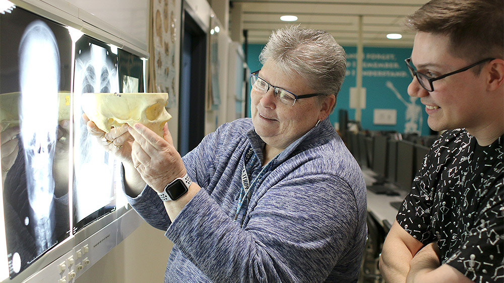 Instructor and a student looking at a model of a skull in front of a wall of CT scans