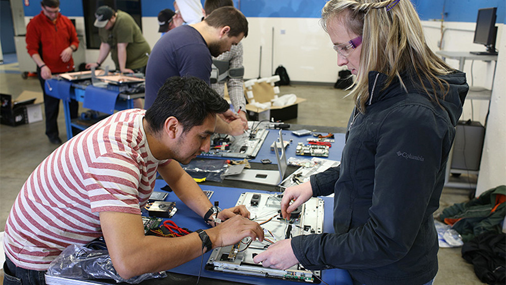 Students working on computer hardware together