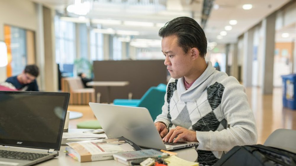 Student working on laptop in study area