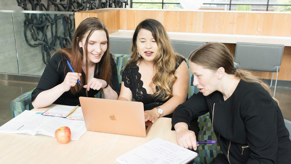 Three women working together around a laptop