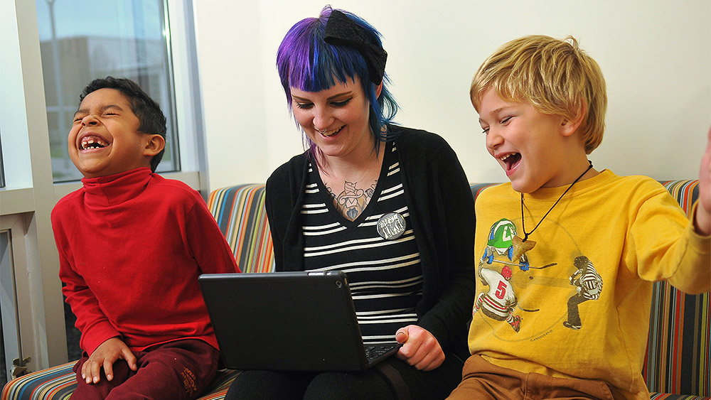 Student working with two children on a laptop, all three are laughing
