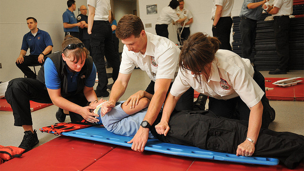 Students in a training simulation with another student acting with a spinal injury