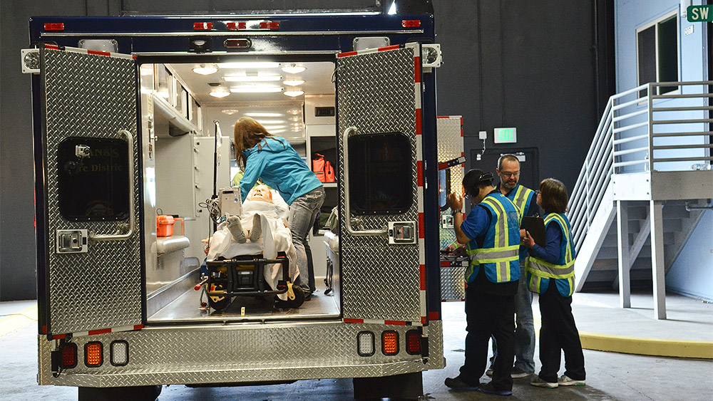 Students putting a dummy into an ambulance in a simulation