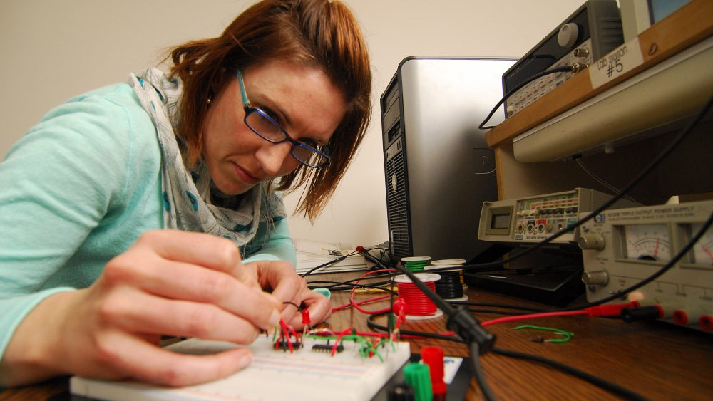 Woman working on engineering project in classroom
