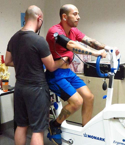 Student riding an exercise bike with another student taking the rider's vitals