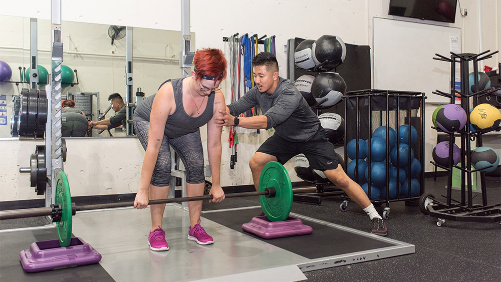 Student working with a personal trainer lifting weights