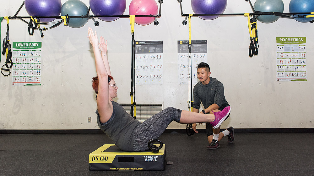 Student working out with an instructor in the gym
