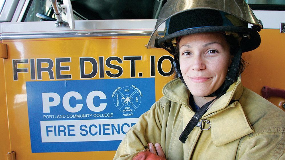 Student in a firefighter uniform standing in front of a fire truck