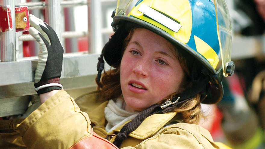 Student in a firefighter uniform working on a fire truck