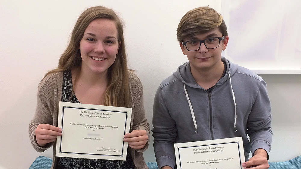 Two students holding their focus awards