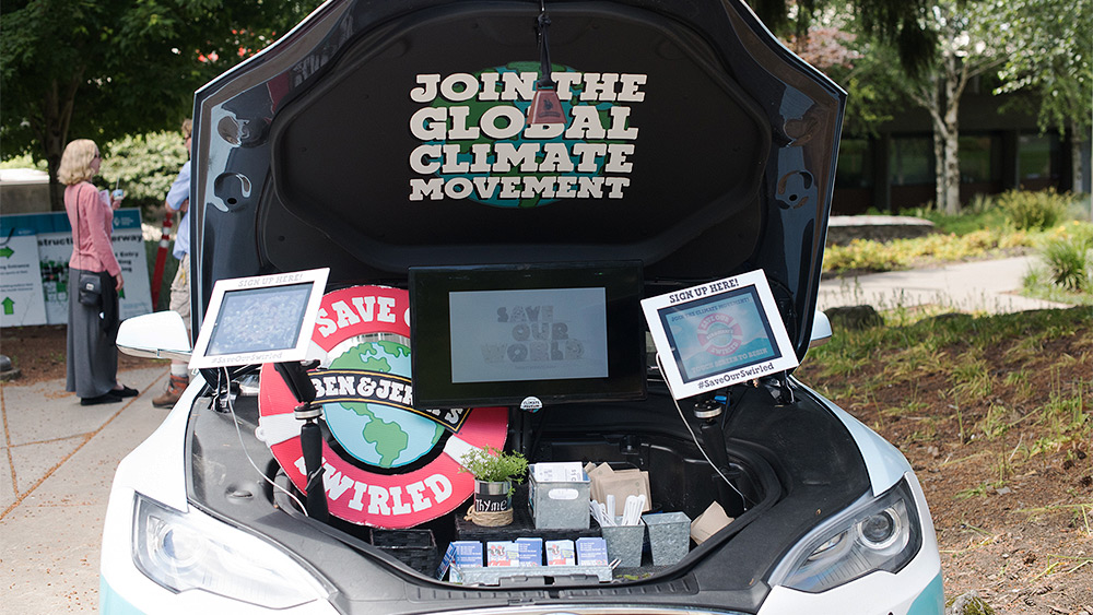 Tesla car with 'Join the global climate movement' poster and various activist materials