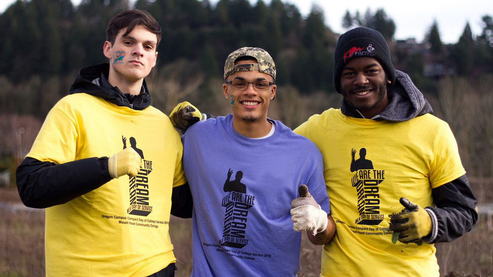 Three students doing work in the community with MLK Day shirts on