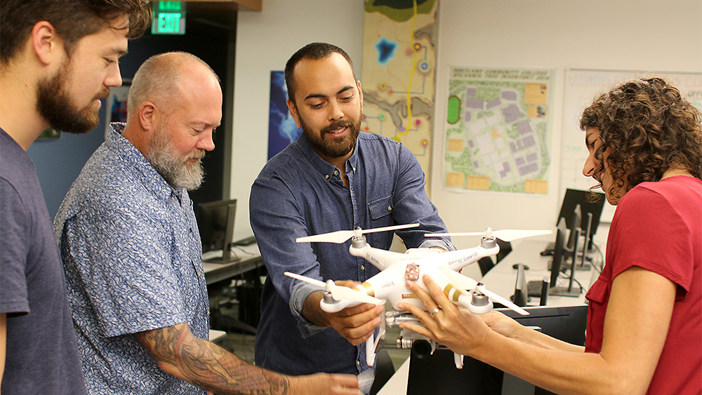 GIS students holding a drone with maps on the wall behind them