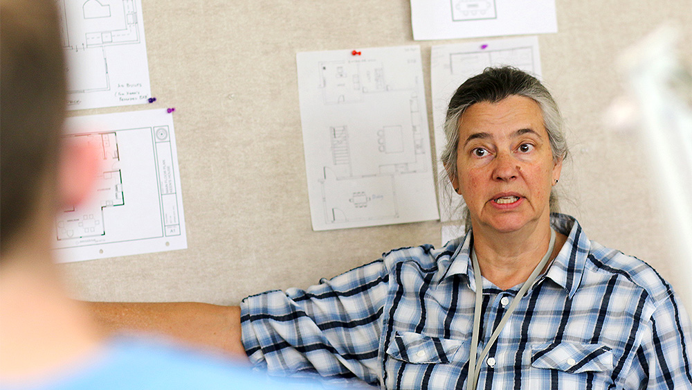 Interior Design instructor teaching in front of a wall of blueprints