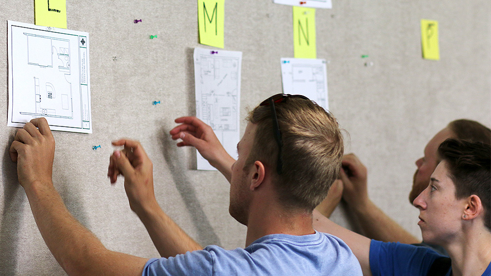 Students looking at multiple kitchen blueprints pinned to a wall