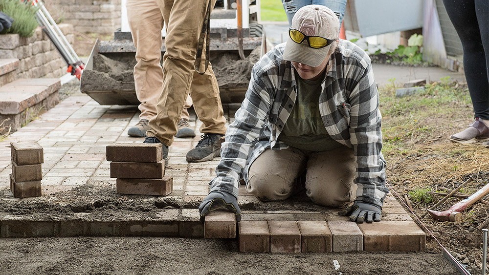 Student laying pavers at a job site for a path
