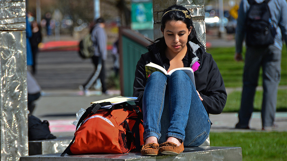 Student reading outside on campus