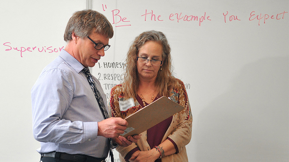 Instructor and a student looking at a clipboard in front of a whiteboard that says 'be the example'