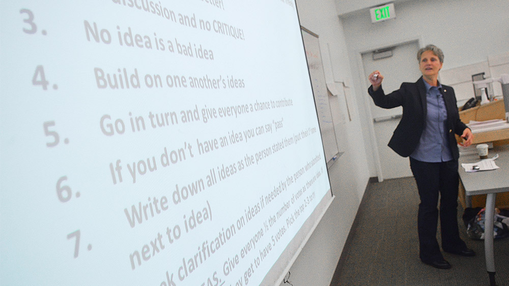 Instructor teaching in front of a whiteboard that says things like 'no idea is a bad idea' and 'build on each other's ideas'