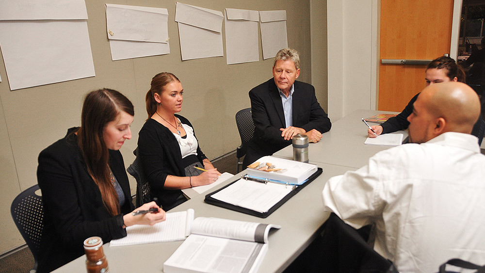 Students sitting around a conference table having a meeting