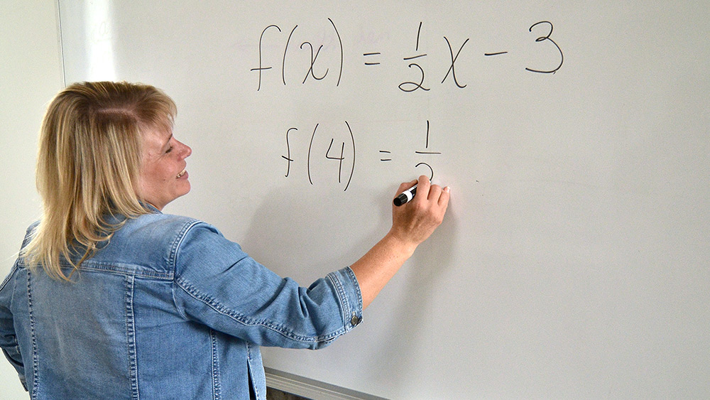 Math instructor writing equations on a whiteboard