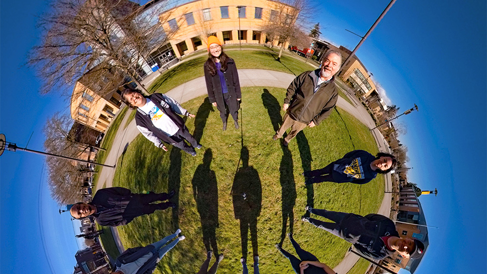 3D fisheye photo of students standing in a circle outside